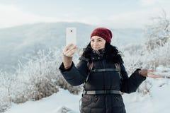 Ο χαμογελώντας θηλυκός τουρίστας έντυσε θερμό παίρνοντας ένα selfie σε ένα χιονώδες γ Στοκ εικόνες με δικαίωμα ελεύθερης χρήσης