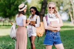Ο χαμογελώντας ξανθός σπουδαστής με το κράτημα ακουστικών κρατά ενώ φίλοι που μιλούν πίσω στο πάρκο Στοκ Εικόνες