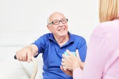 Ο χαμογελώντας πρεσβύτερος φροντίζεται για στην οικιακή φροντίδα στοκ φωτογραφία με δικαίωμα ελεύθερης χρήσης