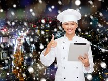 Ο χαμογελώντας αρχιμάγειρας με την παρουσίαση PC ταμπλετών φυλλομετρεί επάνω Στοκ Εικόνες
