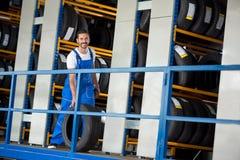 Ο χαμογελώντας αυτόματος μηχανικός έχει πωλήσει μια ρόδα αυτοκινήτων Στοκ Φωτογραφίες