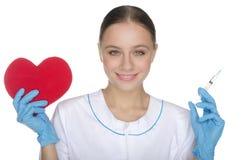 Ο χαμογελώντας γιατρός παρουσιάζει ένα σύμβολο και σύριγγα καρδιών Στοκ Φωτογραφίες