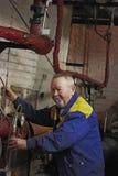 Ο χαμογελώντας ηλικιωμένος μηχανικός ατόμων ελέγχει τον εξοπλισμό Στοκ φωτογραφίες με δικαίωμα ελεύθερης χρήσης