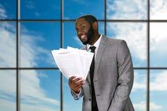 Ο χαμογελώντας μαύρος επιχειρηματίας κρατά τις συμβάσεις Στοκ Φωτογραφίες