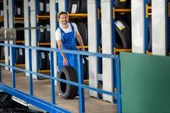 Ο χαμογελώντας μηχανικός ωθεί τη ρόδα αυτοκινήτων Στοκ Εικόνα