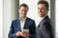 Ο χαμογελώντας νέος επιχειρηματίας που εξετάζει τη κάμερα, εφαρμογή αναπτύσσεται Στοκ Εικόνες