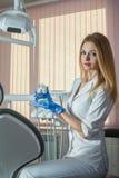 Ο χαμογελώντας νέος οδοντίατρος κρατά το σαγόνι παιχνιδιών στο γραφείο της οδοντικής κλινικής Στοκ Φωτογραφίες