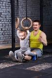 Ο χαμογελώντας νέος πατέρας εκπαιδεύει το μικρό γιο με τα gimnastic δαχτυλίδια ενάντια στο τουβλότοιχο στη γυμναστική Στοκ φωτογραφίες με δικαίωμα ελεύθερης χρήσης
