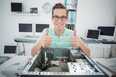 Ο χαμογελώντας τεχνικός που εργάζεται στη σπασμένη παρουσίαση υπολογιστών φυλλομετρεί επάνω Στοκ φωτογραφία με δικαίωμα ελεύθερης χρήσης
