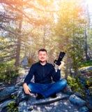 Ο χαμογελώντας φωτογράφος με τη κάμερα στη γιόγκα θέτει Στοκ Φωτογραφίες