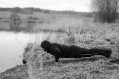 Ο χαρισματικός αθλητικός τύπος κάνει τις αθλητικές ασκήσεις από τη λίμνη στοκ εικόνα
