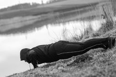 Ο χαρισματικός αθλητικός τύπος κάνει τις αθλητικές ασκήσεις από τη λίμνη στοκ εικόνες με δικαίωμα ελεύθερης χρήσης