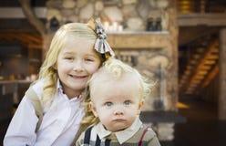 Ο χαριτωμένοι αδελφός και η αδελφή θέτουν στην αγροτική καμπίνα Στοκ εικόνα με δικαίωμα ελεύθερης χρήσης