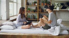 Ο χαριτωμένοι σύζυγος και η σύζυγος ζευγών έχουν τη διασκέδαση με τα αυξημένα γυαλιά πραγματικότητας, το άτομο φορά τα γυαλιά και απόθεμα βίντεο