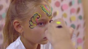 Ο χαριτωμένος έφηβος κοριτσιών που λαμβάνει το πολύχρωμο πρόσωπο aquagrim με ακτινοβολεί και διαμάντια απόθεμα βίντεο