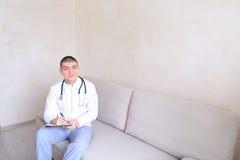 Ο χαριτωμένος γιατρός κούμπωσε ομοιόμορφο και ήταν έτοιμος να λάβει τους ασθενείς s Στοκ Εικόνες