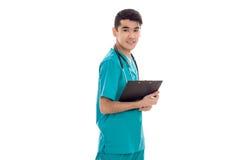 Ο χαριτωμένος γιατρός νεαρών άνδρων μπλε σε ομοιόμορφο με το stethoscop στο λαιμό του smilind και καθιστά τις σημειώσεις απομονωμ Στοκ Φωτογραφία