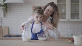 Ο χαριτωμένος γιος πορτρέτου βοηθά mom στην κουζίνα Το αγόρι παρεμποδίζει το γάλα σε μια χρησιμοποίηση κύπελλων γυαλιού χτυπά ελα απόθεμα βίντεο