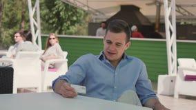 Ο χαριτωμένος επιχειρηματίας εξετάζει το businesscard στο café κοντά στη λίμνη απόθεμα βίντεο