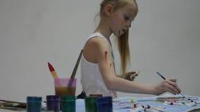 Ο χαριτωμένος ζωγράφος μικρών κοριτσιών επισύρει την προσοχή στον πίνακα και σε τον στα ενδύματά της o απόθεμα βίντεο