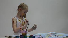 Ο χαριτωμένος ζωγράφος μικρών κοριτσιών επισύρει την προσοχή στον πίνακα και σε τον στα ενδύματά της o φιλμ μικρού μήκους
