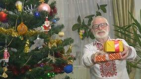 Ο χαριτωμένος ηληκιωμένος κρατά τα χριστουγεννιάτικα δώρα κοντά στο χριστουγεννιάτικο δέντρο απόθεμα βίντεο