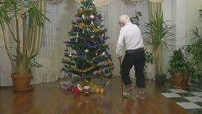 Ο χαριτωμένος ηληκιωμένος στα παραδοσιακά ενδύματα χορεύει κοντά στο χριστουγεννιάτικο δέντρο σε σε αργή κίνηση απόθεμα βίντεο