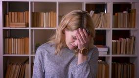 Ο χαριτωμένος μέσης ηλικίας ξανθός δάσκαλος καλύπτει το πρόσωπο στη χειρονομία facepalm έντονα που ενοχλείται στη βιβλιοθήκη απόθεμα βίντεο