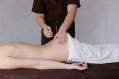 Ο χαριτωμένος μασέρ τύπων ζυμώνει πίσω του θηλυκού ασθενή που βρίσκεται στον καναπέ Στοκ Εικόνες