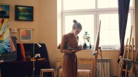 Ο χαριτωμένος νέος ζωγράφος γυναικών εργάζεται στην παλέτα εκμετάλλευσης στούντιο και χρωματίζει στον καμβά που συγκεντρώνεται στ απόθεμα βίντεο