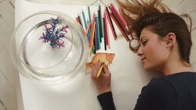 Ο χαριτωμένος νέος θηλυκός καλλιτέχνης κάνει μια εικόνα λίγου χρυσού ψαριού να κλείσει επάνω Τοπ όψη φιλμ μικρού μήκους