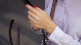 Ο χαριτωμένος σπουδαστής στο μαύρο περίπατο sunglassesin στην οδό και η συζήτηση στο κύτταρό της τηλεφωνούν απόθεμα βίντεο