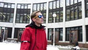 Ο χαριτωμένος τύπος στα κόκκινα αθλητικά ενδύματα και τα γυαλιά ηλίου χορεύει δίπλα στο μεγάλο γκρίζο κτήριο απόθεμα βίντεο