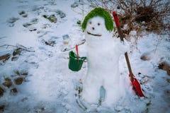 Ο χαριτωμένος χαμογελώντας χιονάνθρωπος στην πράσινη ΚΑΠ του Στοκ Εικόνες