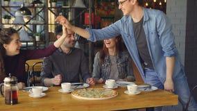 Ο χαρούμενος άνδρας στα περιστασιακά ενδύματα εκπλήσσει τη νέα γυναίκα στην ξαφνική άφιξη στον καφέ, το κορίτσι είναι συγκινημένο απόθεμα βίντεο