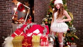 Ο χαρούμενος αρωγός Santa ` s παρουσιάζει δώρα, στο νέο μέρος δωματίων έτους ` s των φωτεινών εκπλήξεων για τα παιδιά, το κορίτσι απόθεμα βίντεο