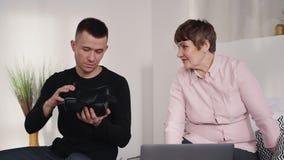 Ο χαρούμενος εγγονός μιλά και παρουσιάζει στην ανώτερη γυναίκα πώς να χρησιμοποιήσει vr τα γυαλιά απόθεμα βίντεο