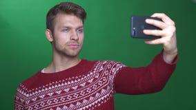 Ο χαρούμενος επιχειρηματίας κάνει selfies στο smartphone με το θετικό χαμόγελο στο πράσινο υπόβαθρο φιλμ μικρού μήκους