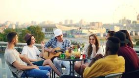 Ο χαρούμενος μουσικός παίζει την κιθάρα με τους φίλους του που τραγουδούν και τη συνεδρίαση γέλιου στη στέγη στον πίνακα ψυχαγωγί απόθεμα βίντεο
