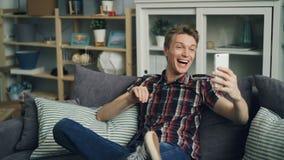 Ο χαρούμενος νεαρός άνδρας κάνει τη σε απευθείας σύνδεση τηλεοπτική κλήση χρησιμοποιώντας το smartphone που μιλά και που εξετάζει απόθεμα βίντεο