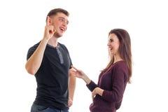 Ο χαρούμενος νεαρός άνδρας στέκεται με το εύθυμο κορίτσι του και αυξάνει ένα δάχτυλο επάνω Στοκ Εικόνες