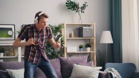 Ο χαρούμενος σπουδαστής νεαρών άνδρων χορεύει στο σπίτι με το φλυτζάνι του τσαγιού και του smartphone ακούοντας τη μουσική μέσω τ απόθεμα βίντεο