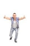 Ο χαρούμενος τύπος με μια τοποθέτηση, δόσιμο φυλλομετρεί επάνω Στοκ Φωτογραφίες