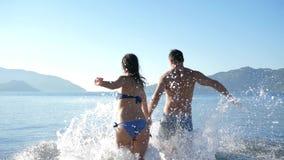 Ο χαρούμενος τύπος με το κορίτσι στη διασκέδαση μπικινιών ξοδεύει το χρόνο στο νερό στο παραθαλάσσιο θέρετρο στις διακοπές απόθεμα βίντεο