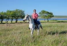 Ο χαρούμενος τύπος οδηγά στην πλάτη αλόγου πέρα από τον τομέα, ενάντια στο σκηνικό της λίμνης Στοκ εικόνες με δικαίωμα ελεύθερης χρήσης