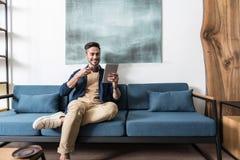 Ο χαρωπός γενειοφόρος τύπος που έχει χαλαρώνει το χρόνο στο καθιστικό του στοκ εικόνα με δικαίωμα ελεύθερης χρήσης