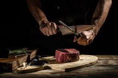 Ο χασάπης αρχιμαγείρων προετοιμάζει την μπριζόλα βόειου κρέατος στοκ εικόνες με δικαίωμα ελεύθερης χρήσης