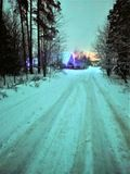 Ο χειμερινός δρόμος στο χειμερινό δάσος, το σπίτι, φωτεινές εορταστικές γιρλάντες χρώματος ανάβει την περιοχή, είσοδος μέσα σε το στοκ εικόνες