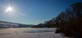 Ο χειμερινός ποταμός που καλύπτεται με τον πάγο και το χιόνι σε μια σαφή ηλιόλουστη ημέρα Στοκ Εικόνες