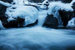 Ο χειμερινός ποταμός, το τοπίο που συλλαμβάνεται από μια θολωμένη μετακίνηση και που πλαισιώνεται από τον μπλε πάγο Στοκ Φωτογραφία